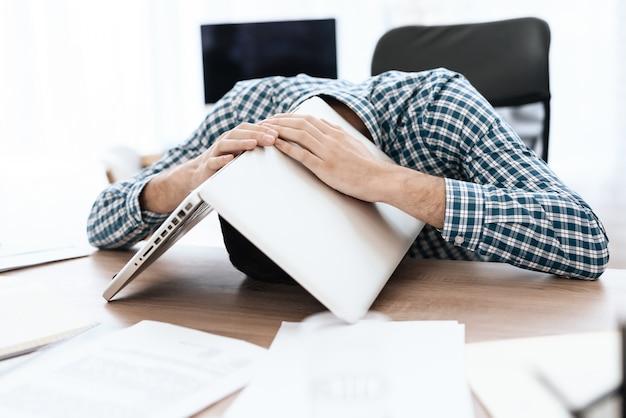 Een man heeft hoofdpijn. hij bedekte zijn hoofd met papieren.