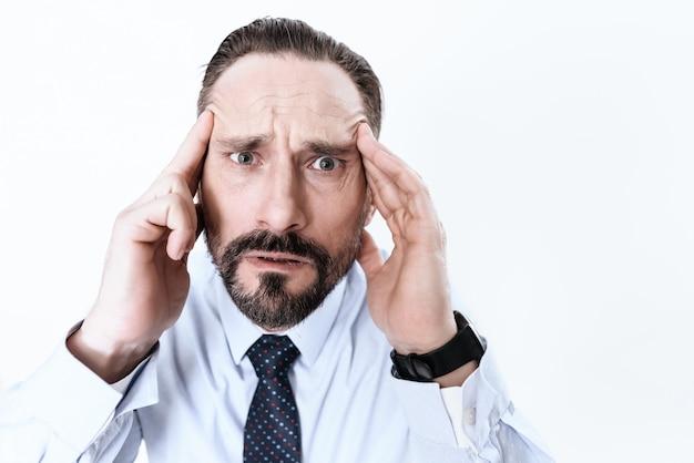 Een man heeft hoofdpijn. hij houdt zijn handen op zijn hoofd.