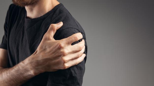 Een man heeft schouderpijn op een grijze achtergrond