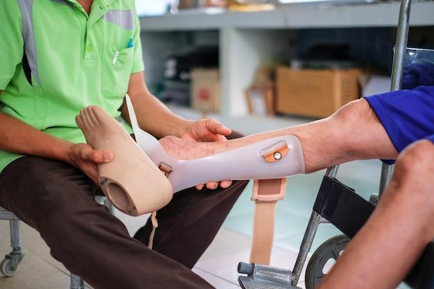Een man helpt invaliden met het maken van nieuwe prothesen om in het ziekenhuis te wandelen.