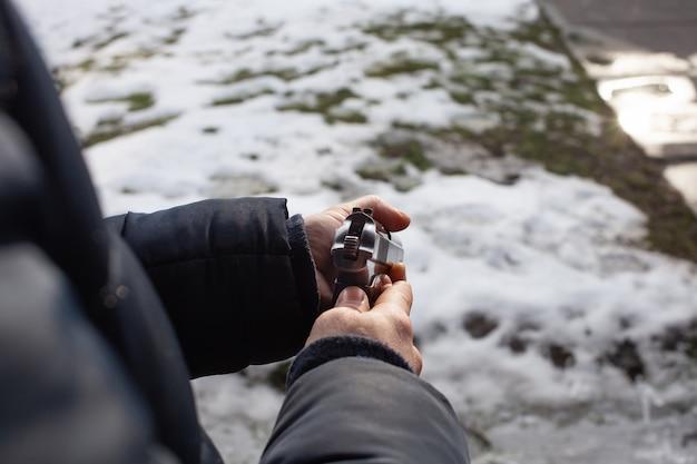 Een man herlaadt een pistool in een streep buiten de deur