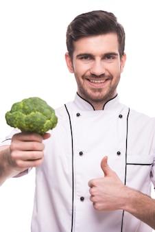 Een man houdt broccoli in zijn hand en vertoont een superteken.
