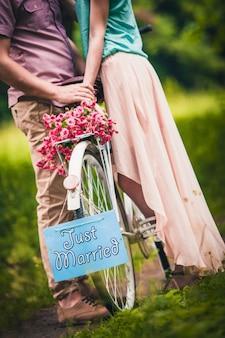 Een man houdt de hand van de vrouw in de buurt van een fiets met een mand met rozen en een inscriptie in het park