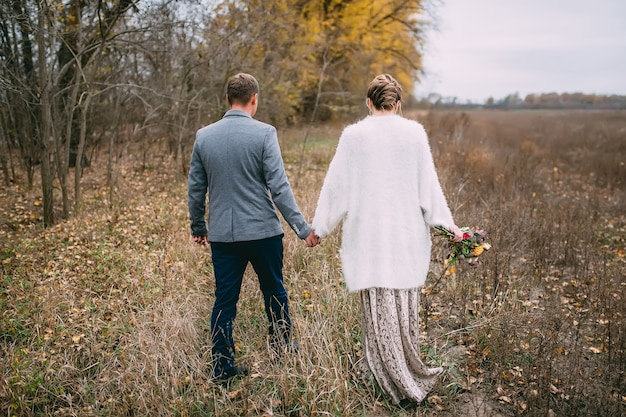 Een man houdt de hand van een vrouw vast in een open uitzicht vanaf de achterkant