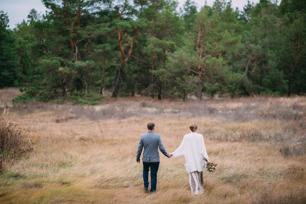 Een man houdt de hand van een vrouw vast op de achtergrond van een bos