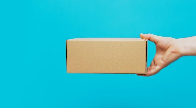 Een man houdt dozen in zijn handen op een blauwe achtergrond. service levering van goederen. bezorgservice in de stad.