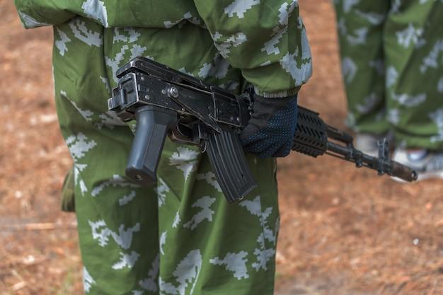 Een man houdt een automatisch wapen in zijn handen, soldaat in uniform gericht met aanvalsgeweer buitenshuis, airsoft