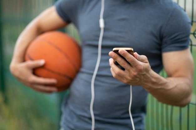 Een man houdt een basketbal in zijn hand, kijkt naar een smartphone en luistert naar muziek met een koptelefoon op straat van dichtbij
