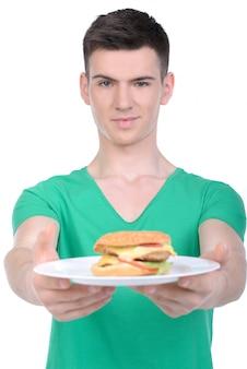 Een man houdt een bord met een hamburger in zijn handen en glimlacht.