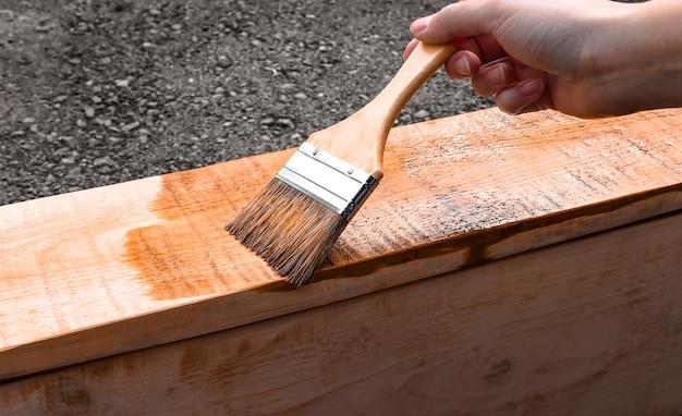 Een man houdt een borstel voor het schilderen van hout in zijn hand huishoudelijk werk dat een houten product bedekt met verf