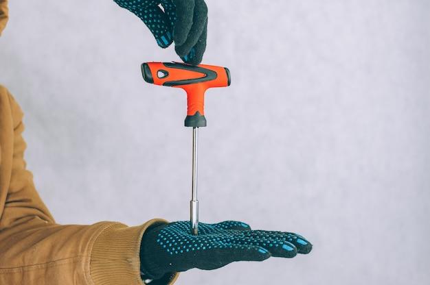 Een man houdt een bouwschroevendraaier in zijn handen aan een lamp.