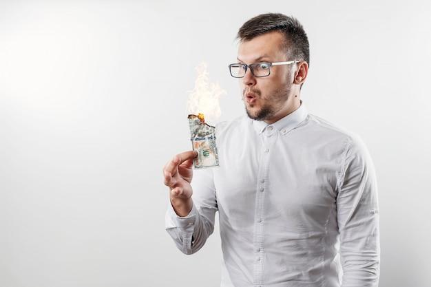 Een man houdt een brandende geldrekening in zijn hand