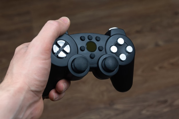 Een man houdt een draadloze gamepad van een videogameconsole in zijn hand