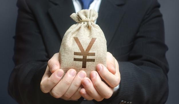 Een man houdt een geldzak voor de yen yuan voor.
