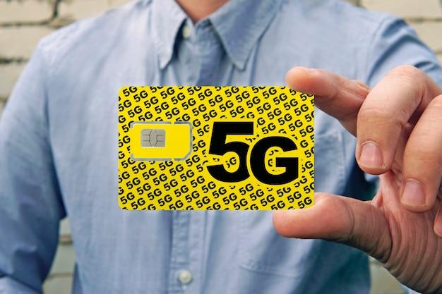 Een man houdt een gele simkaart met het opschrift 5g voor mobiele telefoon in zijn hand. simkaart vervangen en overstappen op snel internet.