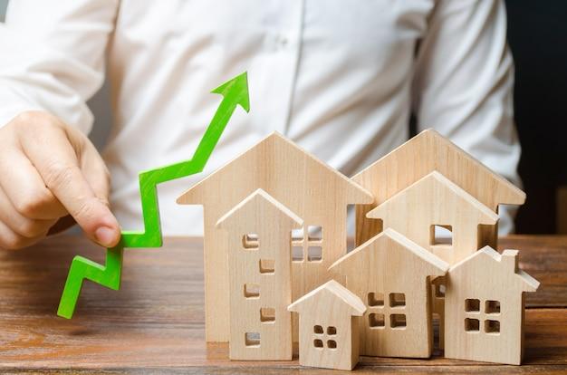Een man houdt een groene pijl omhoog in de buurt van een stel huizen of een stad. groei-indicatoren van de stad