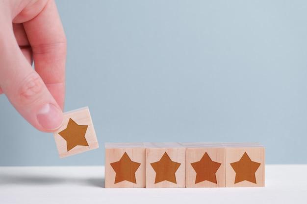 Een man houdt een houten kubus in zijn hand en wil een waardering van vijf sterren geven. de hoogste score.