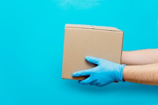 Een man houdt een kartonnen doos vast met zijn hand in een rubberen handschoen. bescherming tegen covid-19. veilige levering van goederen tijdens de coronavirus-epidemie.