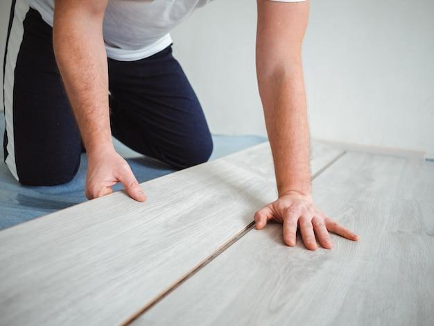 Een man houdt een laminaat in zijn handen. het reparatieproces in de kamer