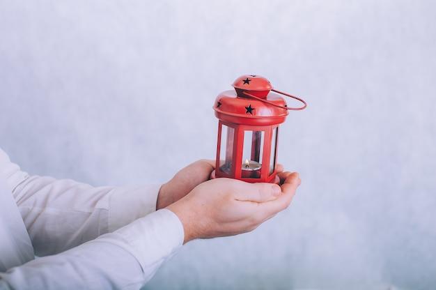 Een man houdt een lamp met een kaars in zijn handen op een wit.
