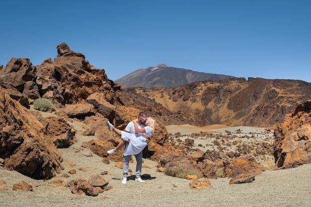 Een man houdt een meisje vast in de krater van de teide-vulkaan
