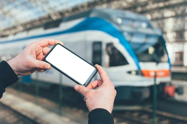 Een man houdt een mock-up van een smartphone vast op de achtergrond van een trein op een treinstation.