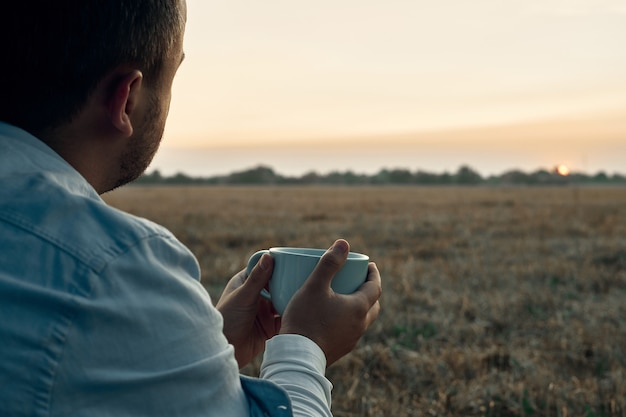 Een man houdt een mok in zijn handen en kijkt naar de dageraad. reiziger, zonsopgang.