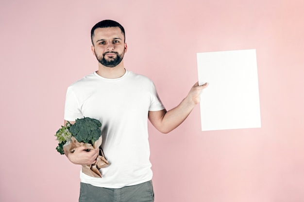 Een man houdt een papieren zak met groenten in zijn handen, kopie ruimte.