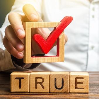 Een man houdt een rood vinkje boven het woord waar. bevestig de waarheid en waarheid. vecht tegen nepnieuws