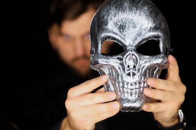 Een man houdt een skeletmasker voor zich wat?