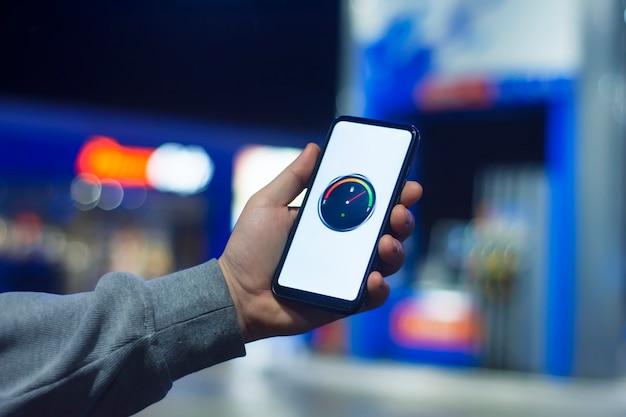 Een man houdt een smartphone met een digitale brandstofmeter op het scherm tegen de achtergrond van een nachttankstation voor een auto.