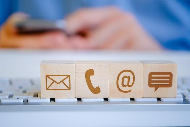 Een man houdt een smartphone met zijn handen vast, op de voorgrond staan houten kubussen met letters, e-mail, telefoon en berichtpictogrammen. het bekijken van inhoud.