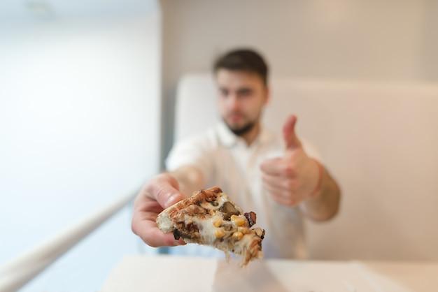 Een man houdt een stuk pizza in zijn handen en toont zijn vinger bij de ingang. een man houdt van pizza. leuk vinden.
