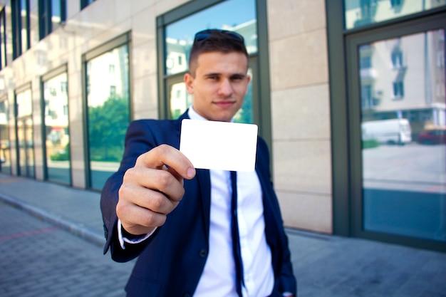 Een man houdt een visitekaartje voor zich copyspace