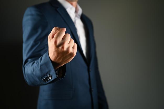 Een man houdt een vuist voor zich vast. een man in een pak toont een kuak naar voren op een zwart veld. concept: kracht in het bedrijfsleven. hoge kwaliteit foto