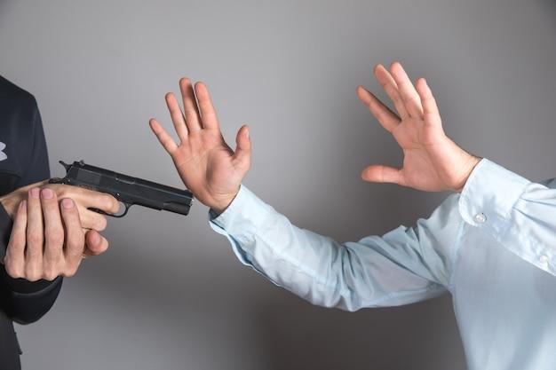 Een man houdt een zwart pistool in zijn hand, dreigt