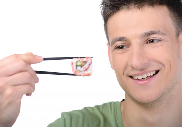 Een man houdt eetstokjes droog en glimlacht.