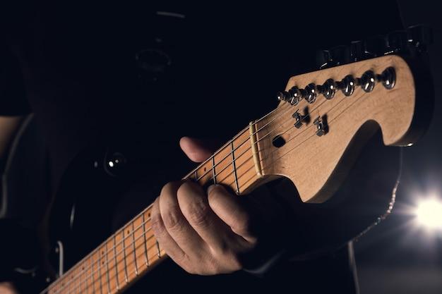 Een man houdt elektrische gitaar op zwarte achtergrond, een selectieve focus op hand.
