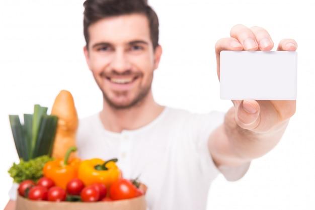 Een man houdt groenten en houdt een tablet vast.