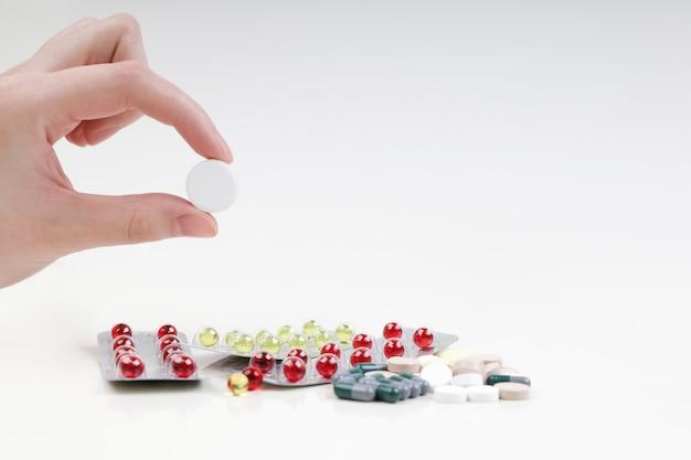 Een man houdt in zijn hand een grote witte pil. een stapel van multi-coloured pillen en capsules op een witte achtergrond. koud en griepseizoen.