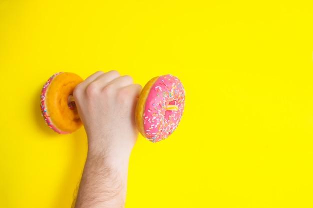 Een man houdt in zijn hand een halter van donuts met roze glazuur op een gele achtergrond