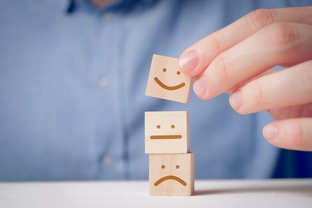 Een man houdt met zijn vingers een houten kubus vast met een positief gezicht naast een ontevreden en neutrale. voor het evalueren van een actie of resource.