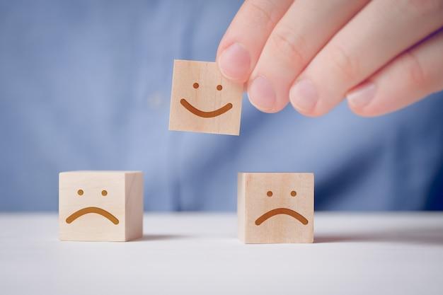 Een man houdt met zijn vingers een houten kubus vast met een positief gezicht naast een ontevreden. voor het evalueren van een actie of resource.