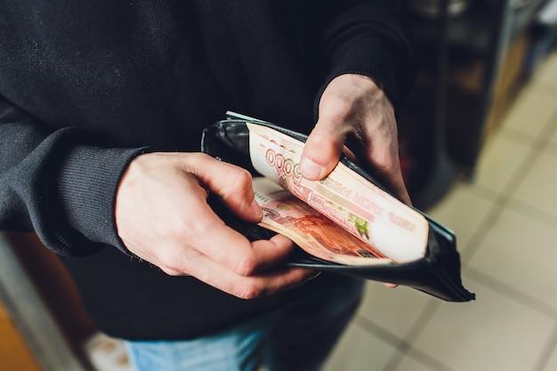 Een man houdt roebels en dollars in zijn hand, een zakenman houdt geld in zijn hand.