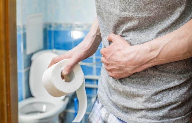 Een man houdt toiletpapier vast. het concept van diarree. aambeien.