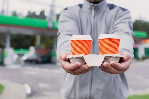 Een man houdt twee kopjes koffie in zijn handen bij een tankstation.