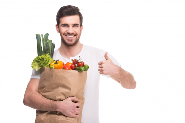 Een man houdt veel groenten in een zak.