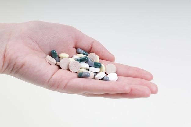 Een man houdt veelkleurige pillen en capsules in de palm van zijn hand. koud en griepseizoen.