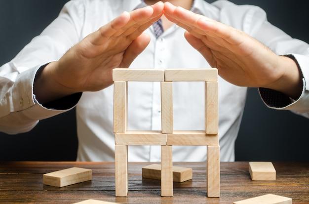 Een man houdt zijn handen in het symbool van het dak boven het bouwen van dominostenen