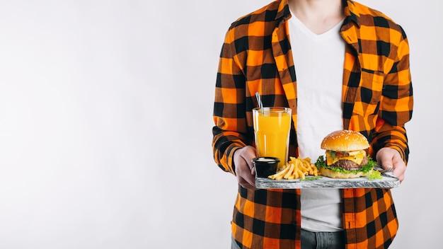 Een man houdt zijn lunch op een dienblad.
